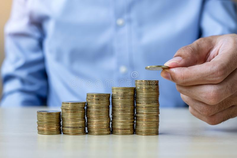 Businessman hand putting golden coin on growing money stairs or stack on wooden table. business, investment, retirement planning,. Finance and Saving for the stock images
