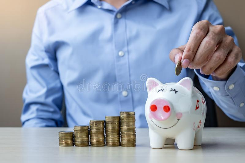 Businessman hand putting golden coin on piggy banking with growing money stairs or stack on wooden table. business, investment,. Retirement planning, finance royalty free stock images