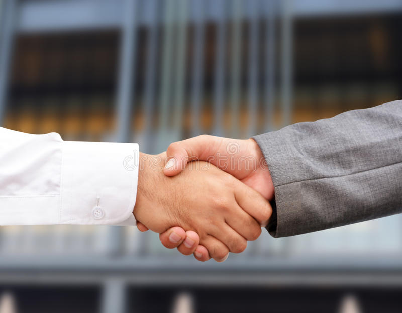 Businessman hand shaking. With urban background stock photography