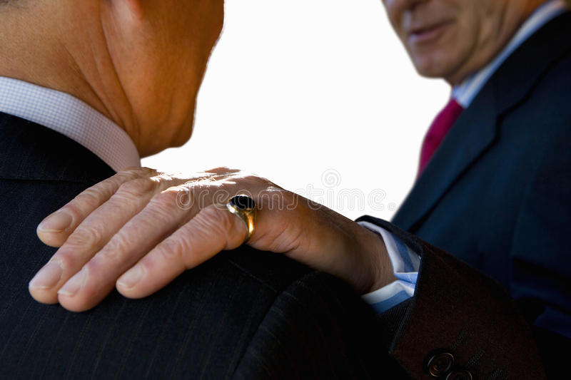 Businessman with hand on shoulder of colleague, close-up, cut out stock photo