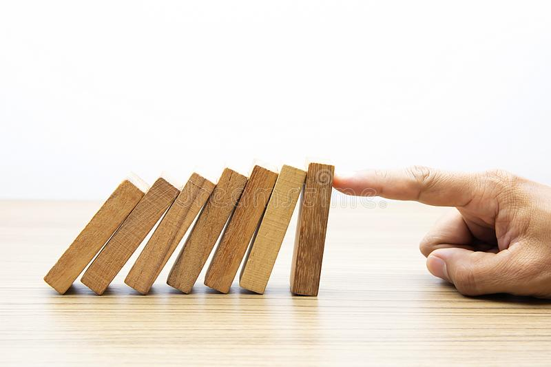 Businessman hand stoped wooden domino effect. royalty free stock images