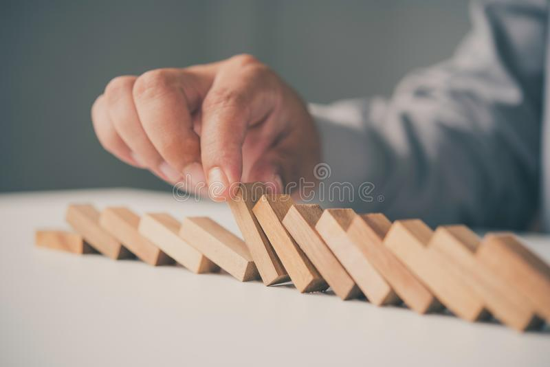 Businessman hand stopping the domino wooden effect concept for b royalty free stock images