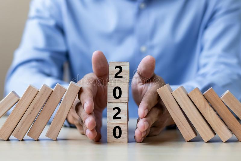 Businessman hand Stopping Falling of 2020 wooden Blocks. Business, Risk Management, Insurance, Resolution, strategy, solution, stock photo