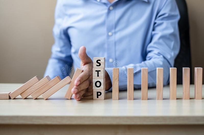 Businessman hand Stopping Falling wooden Blocks or Dominoes. Business, Risk Management, Solution, Insurance and strategy Concepts. Businessman hand Stopping royalty free stock images