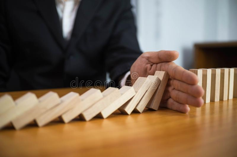 Businessman hand stops domino continuous overturned meaning that hindered business failure. Stop over this business failure royalty free stock photos