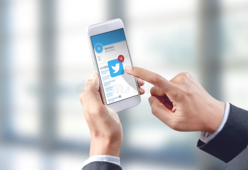 Businessman hand touch twitter icon on mobile screen stock photos