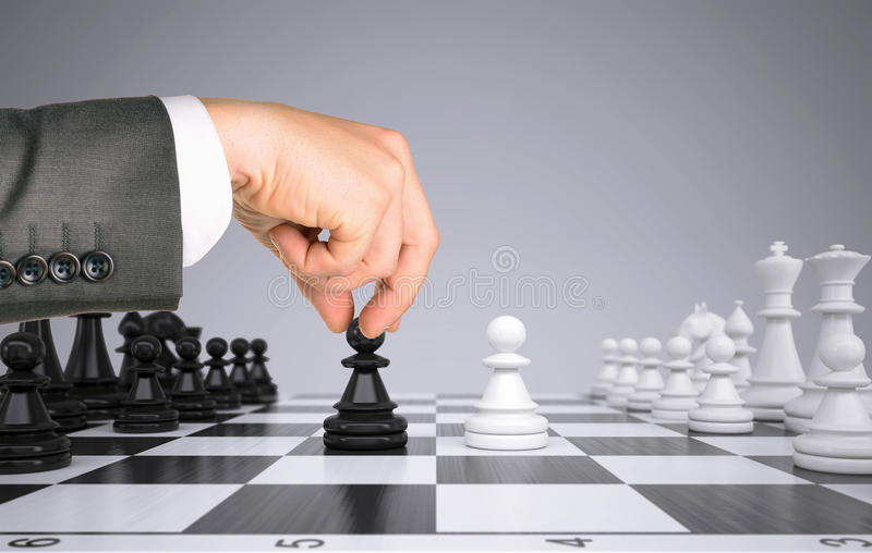 Businessman hand touching pawn figure on chess stock image