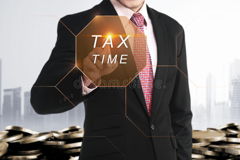 Businessman hand touching Tax Time button royalty free stock photo