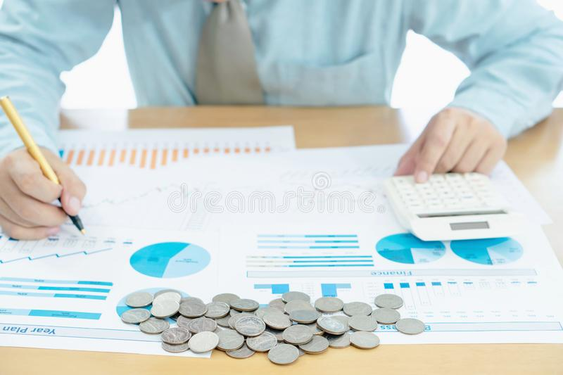 Businessman hand using calculator and reports document financial counting making stock photo