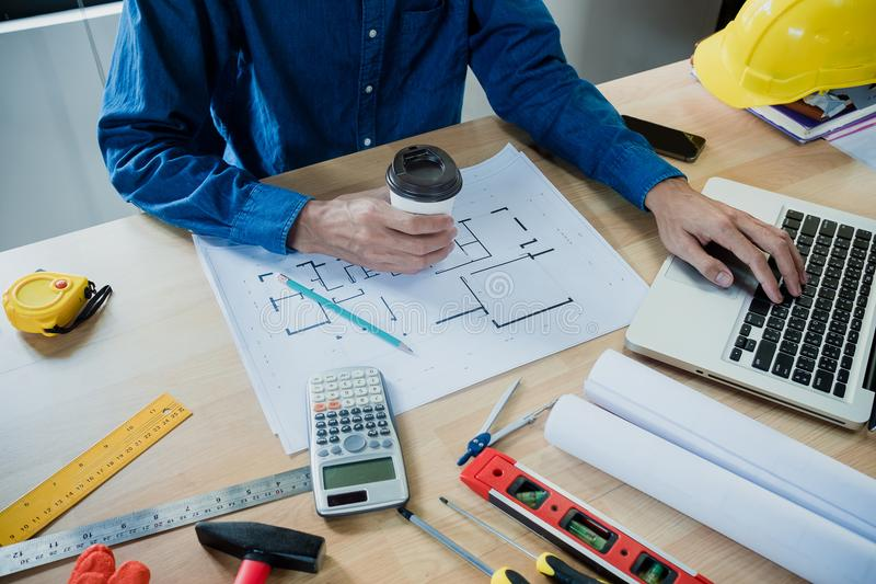 Businessman hand working and holding coffee cup. With laptop and blueprint on architectural project at construction site in office royalty free stock photo