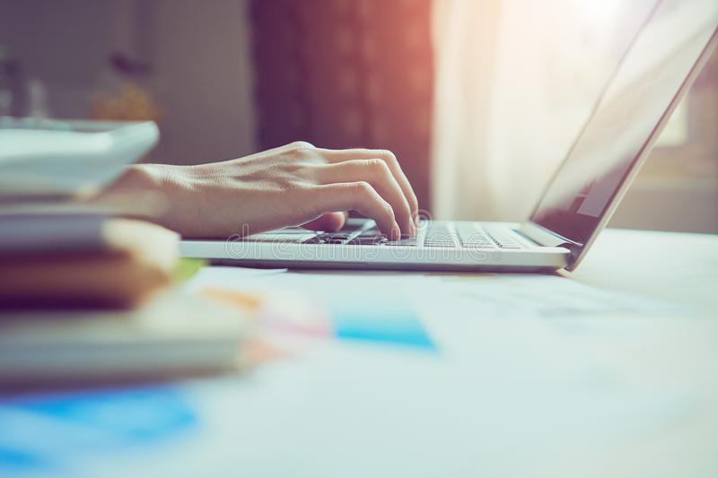 Businessman hand working laptop on wooden desk in office in morning light. stock photography