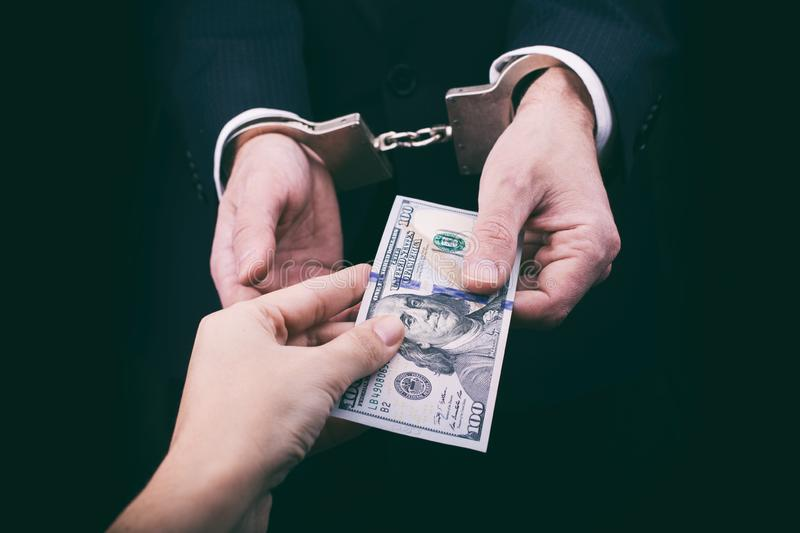 Businessman in handcuffs giving bribe stock photography