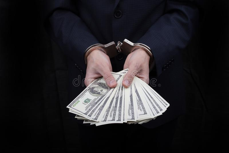 Businessman in handcuffs holding bribe many hundreds dollars stock photography