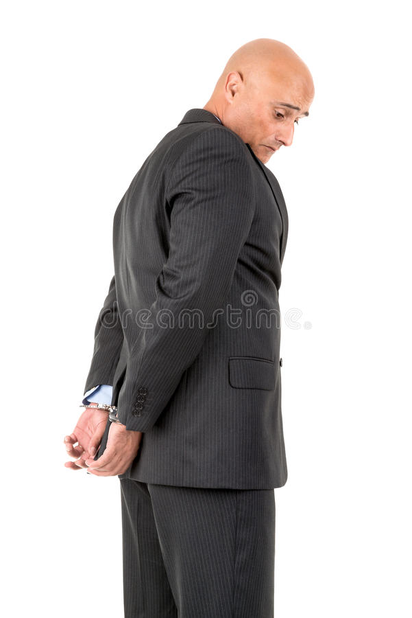 Businessman in handcuffs. Isolated in white background royalty free stock image