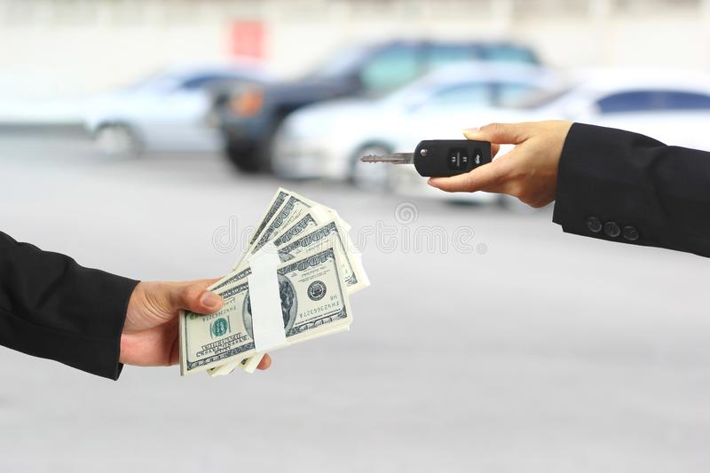 Businessman handed the money to Businesswoman or saleswoman holding in a hand car keys, auto business, car trading, loans for car. Concept stock images