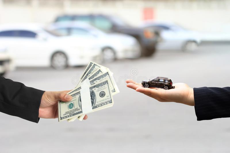 Businessman handed the money to Businesswoman or saleswoman holding miniature car model, auto business, car trading, loans for car. Concept royalty free stock photo