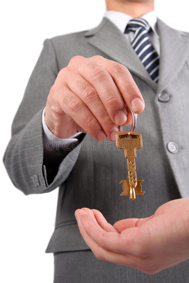 Businessman handing a key stock image
