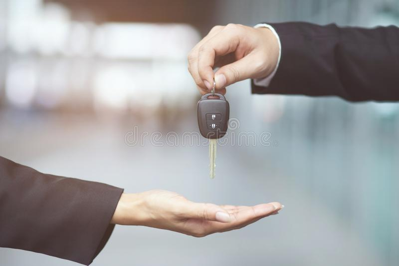 Businessman handing over gives the car key to the other woman on showroom. Car key, businessman handing over gives the car key to the other woman on showroom stock photography