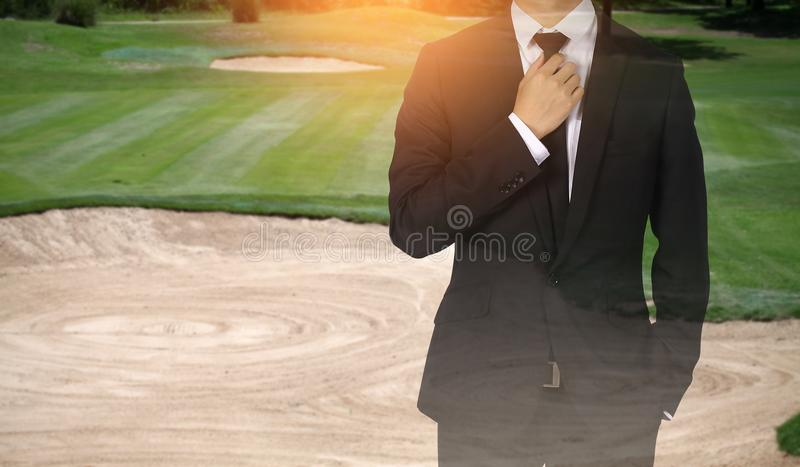 Businessman handles necktie showing confidence in golf course. Businessman handles necktie showing confidence stock photos