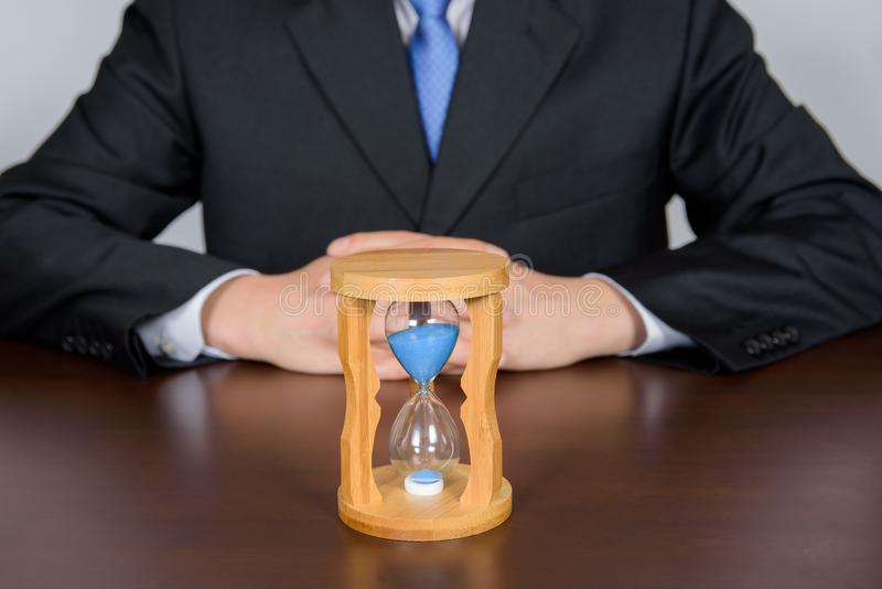 Businessman with hands behind back of an hourglass. stock image