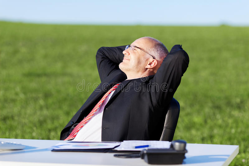 Businessman With Hands Behind Head At Desk On Field stock images