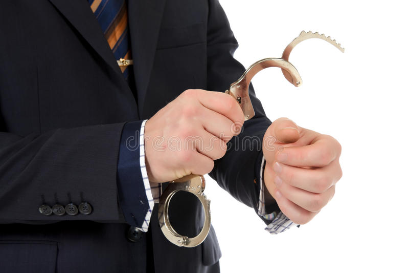 Businessman hands, handcuffs. Businessman who put handcuffs on hands . Studio shot. White background royalty free stock photography