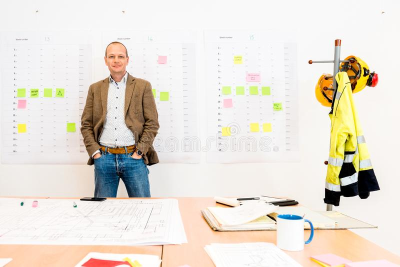 Businessman With Hands In Pockets Standing By Blueprint On Table royalty free stock photography