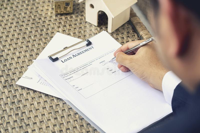 Businessman hands putting signature on document loan agreement, contract for buy new house royalty free stock photography