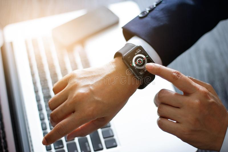 Businessman hands touching smart watch. Using a stock market app and graph on modern virtual screen for business. Technology and f stock image