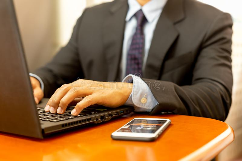 Businessman hands typing on keyboard laptop with cell phone on wooden desk. stock photos