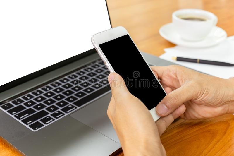Businessman hands using smart phone over laptop at office desk. stock photography