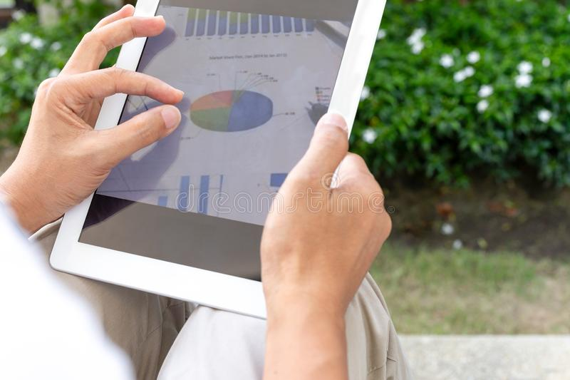 Businessman hands using tablet screen show green graph while working at home in the garden. royalty free stock images
