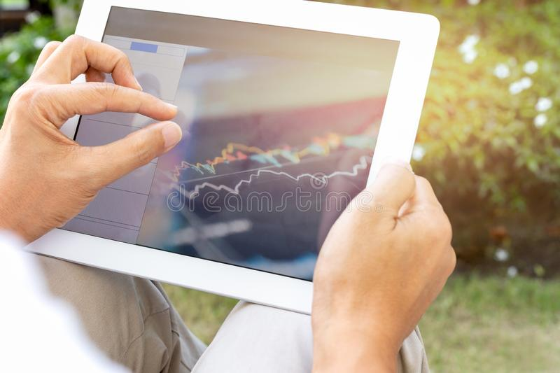 Businessman hands using tablet screen show green graph while working at home in the garden. royalty free stock photography
