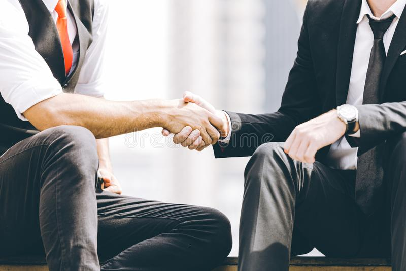 Businessman handshake deal project of business benefits sitting relax outdoor stock image
