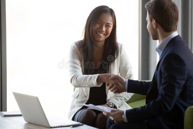 Businessman handshake smiling Asian client closing business deal stock image