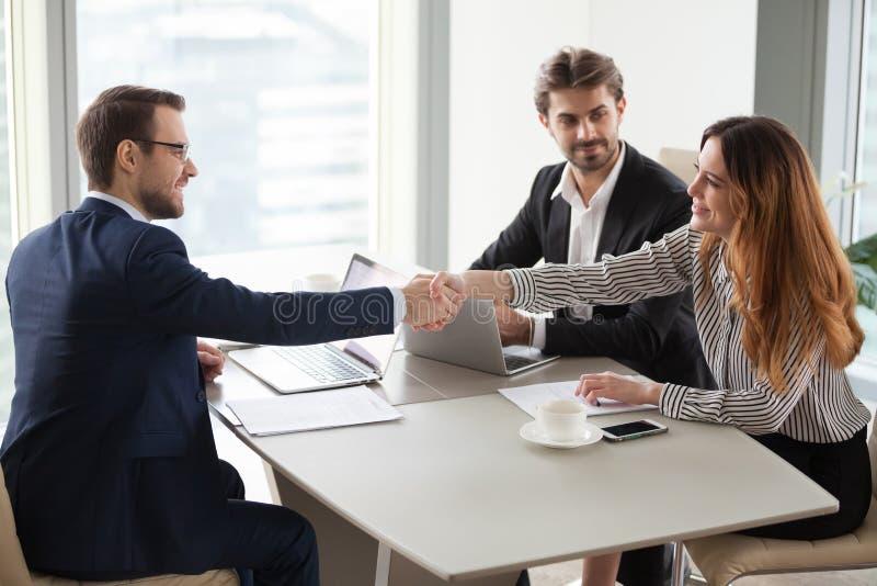 Businessman handshaking businesswoman making deal finishing group negotiations royalty free stock photos