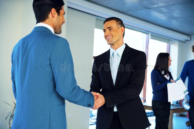 Businessman handshaking in conference hall. Two happy businessman handshaking in conference hall stock images