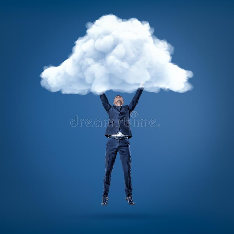 Businessman hanging in the air holding white cloud with both hands royalty free stock images