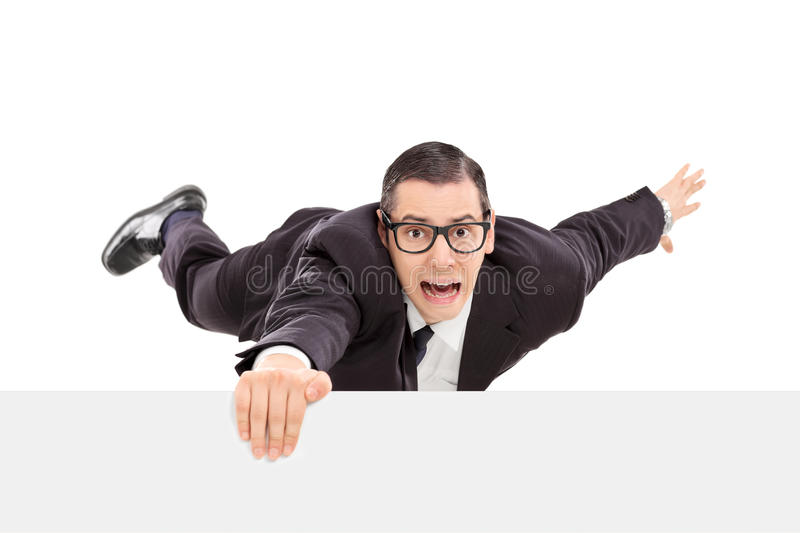 Businessman hanging on the edge of a white panel stock images