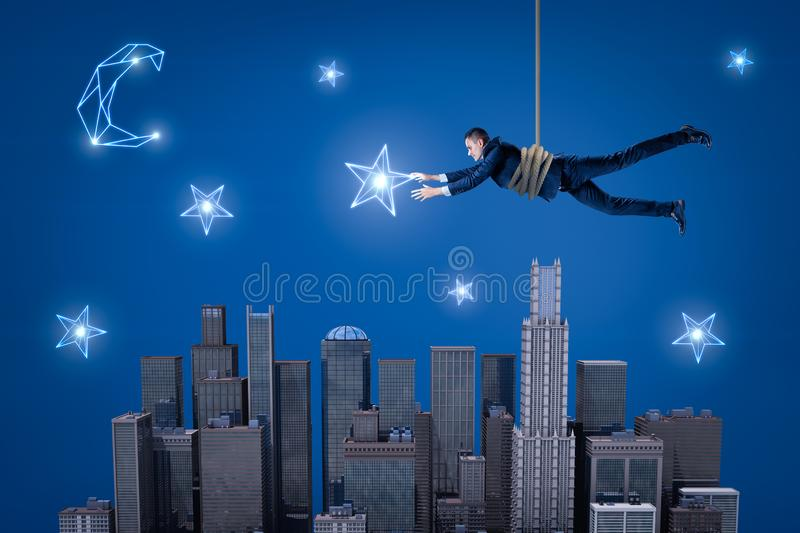 A businessman hanging on a rope above a night city and trying to catch a star in the sky. vector illustration