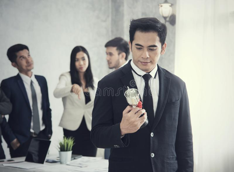 Businessman happy pride with win cup and business team jealous stock photos