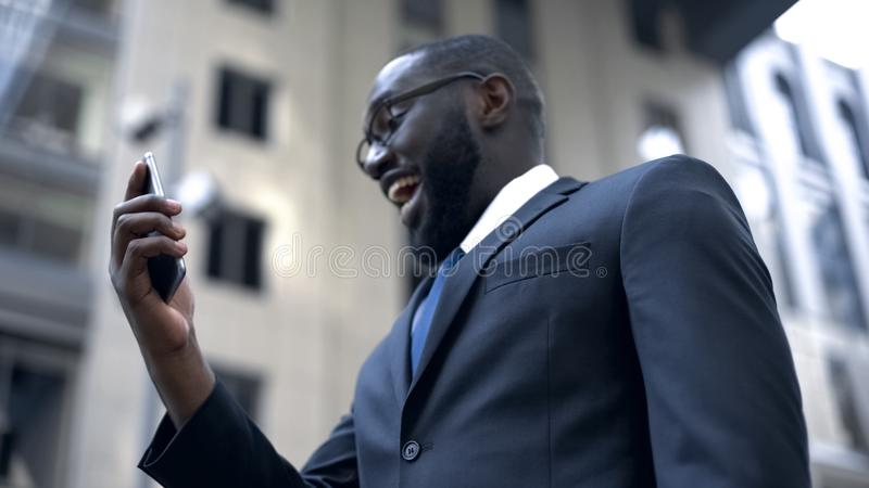 Businessman happy to win money, using smartphone for bets and trading online. Stock photo royalty free stock image