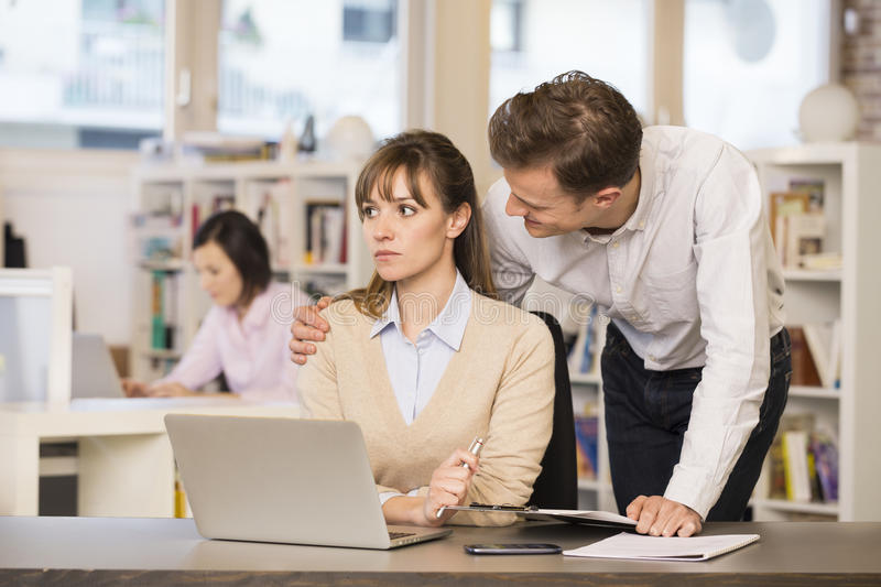 Businessman harassing his colleague at work stock photo