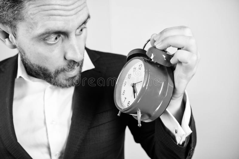Businessman has lack of time. Time management skills. How much time left till deadline. Time to work. Man bearded. Surprised businessman hold clock. Stress stock photography