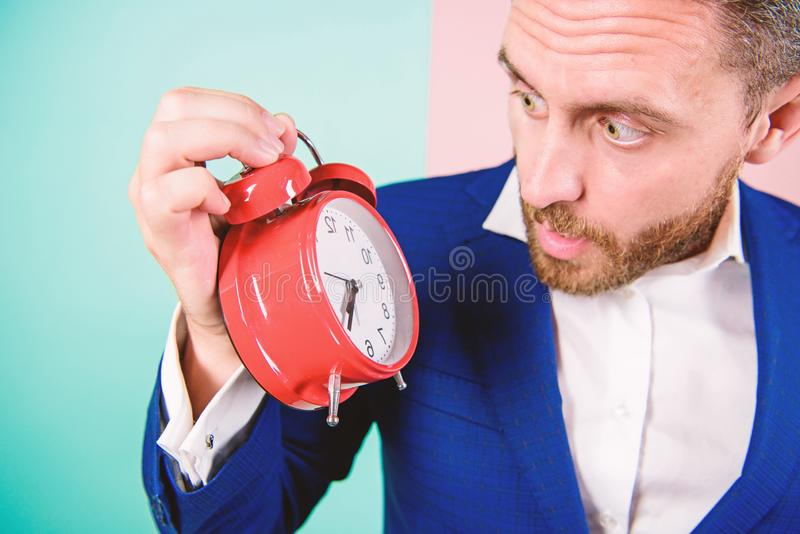 Businessman has lack of time. Time management skills. How much time left till deadline. Time to work. Man bearded. Surprised businessman hold clock. Stress stock photos