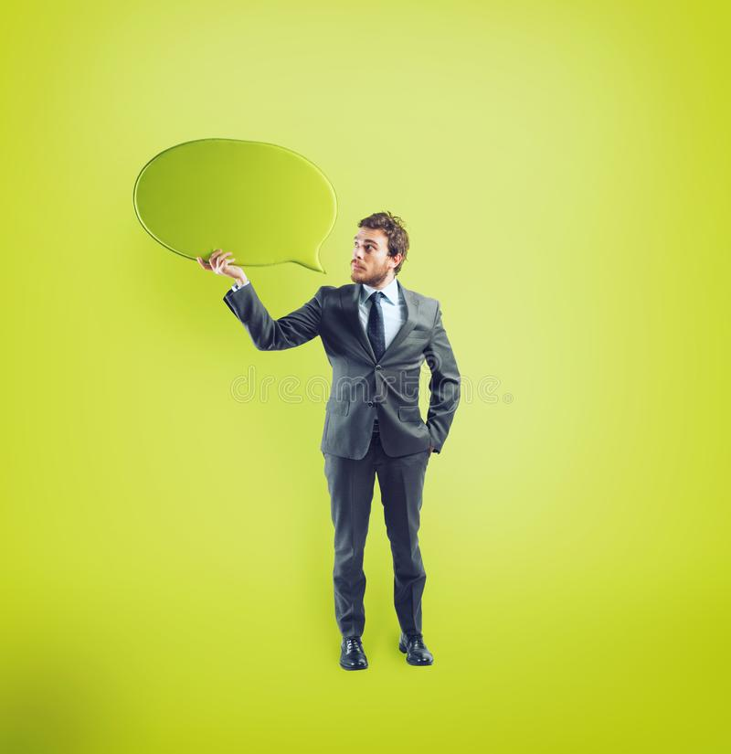 Businessman has something to say in a speech bubble. On green background stock photography