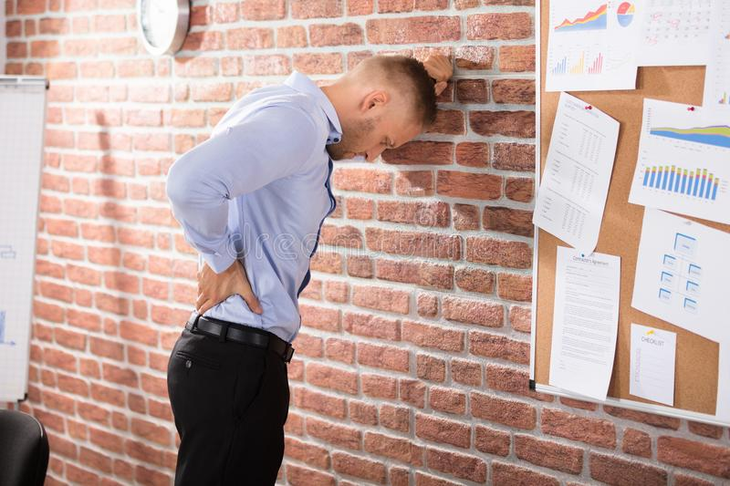 Businessman Having Back Pain In Office. Businessman Leaning Against The Brick Wall Having Back Pain In Office stock photo