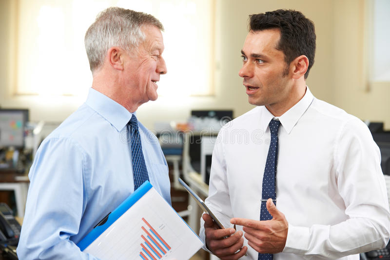 Businessman Having Discussion With Senior Mentor In Office. Businessman Has Discussion With Senior Mentor In Office stock images