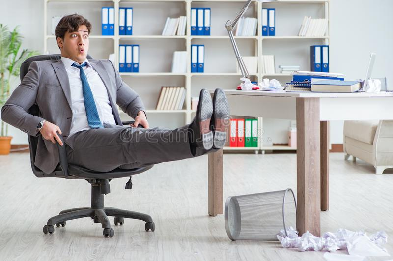 Businessman having fun taking a break in the office at work. The businessman having fun taking a break in the office at work royalty free stock images