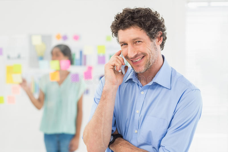 Businessman having phone call while his colleague posing royalty free stock images